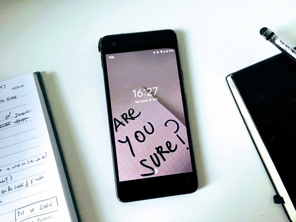 Image of a smartphone with a lock screen wallpaper displaying the message 'Are you sure?'
