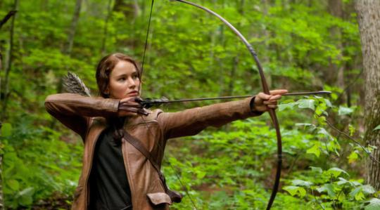 Katniss aiming with her bow in the forest outside district 12